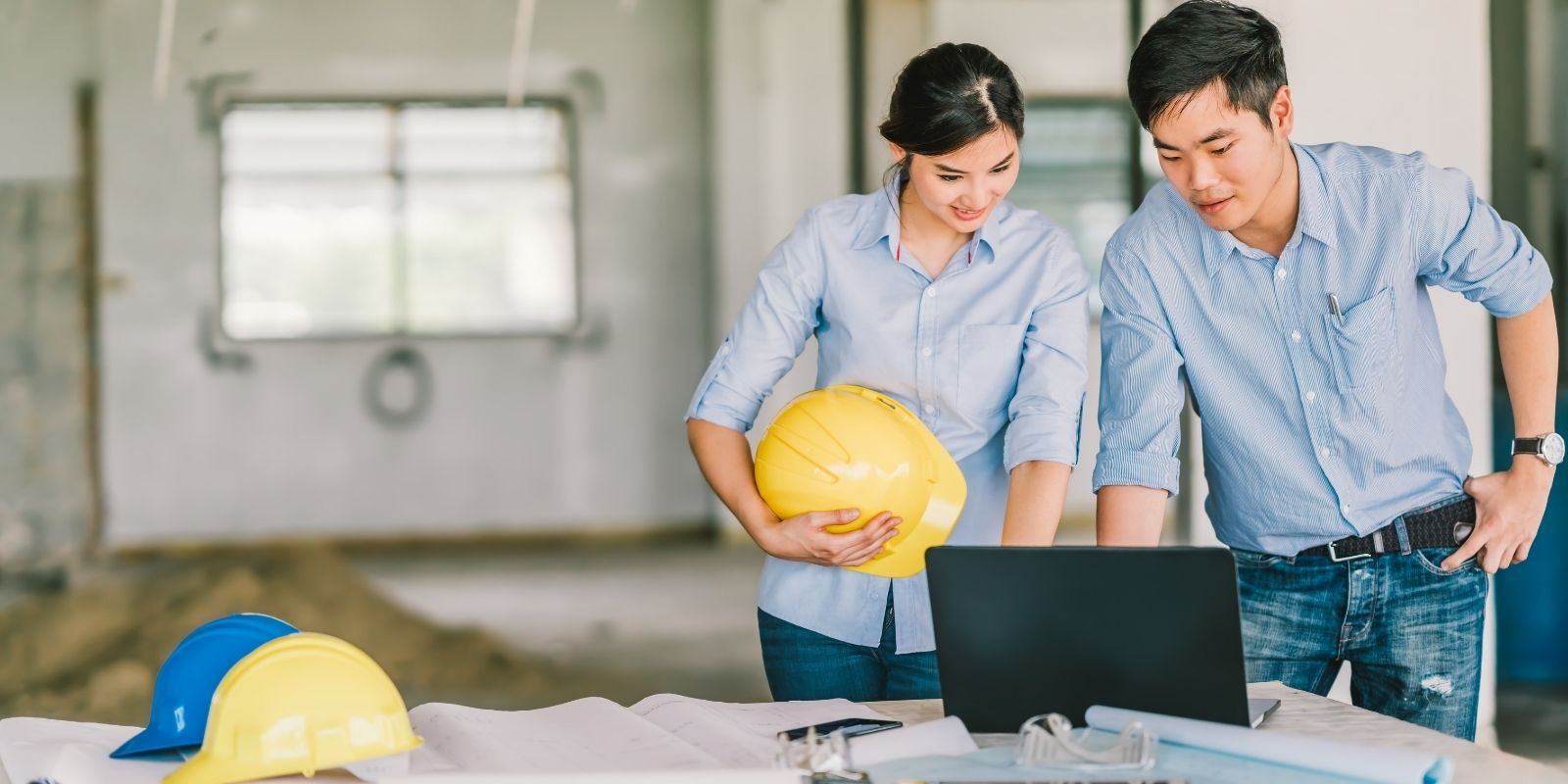 female and male civil engineers look at computer renderings at a construction site