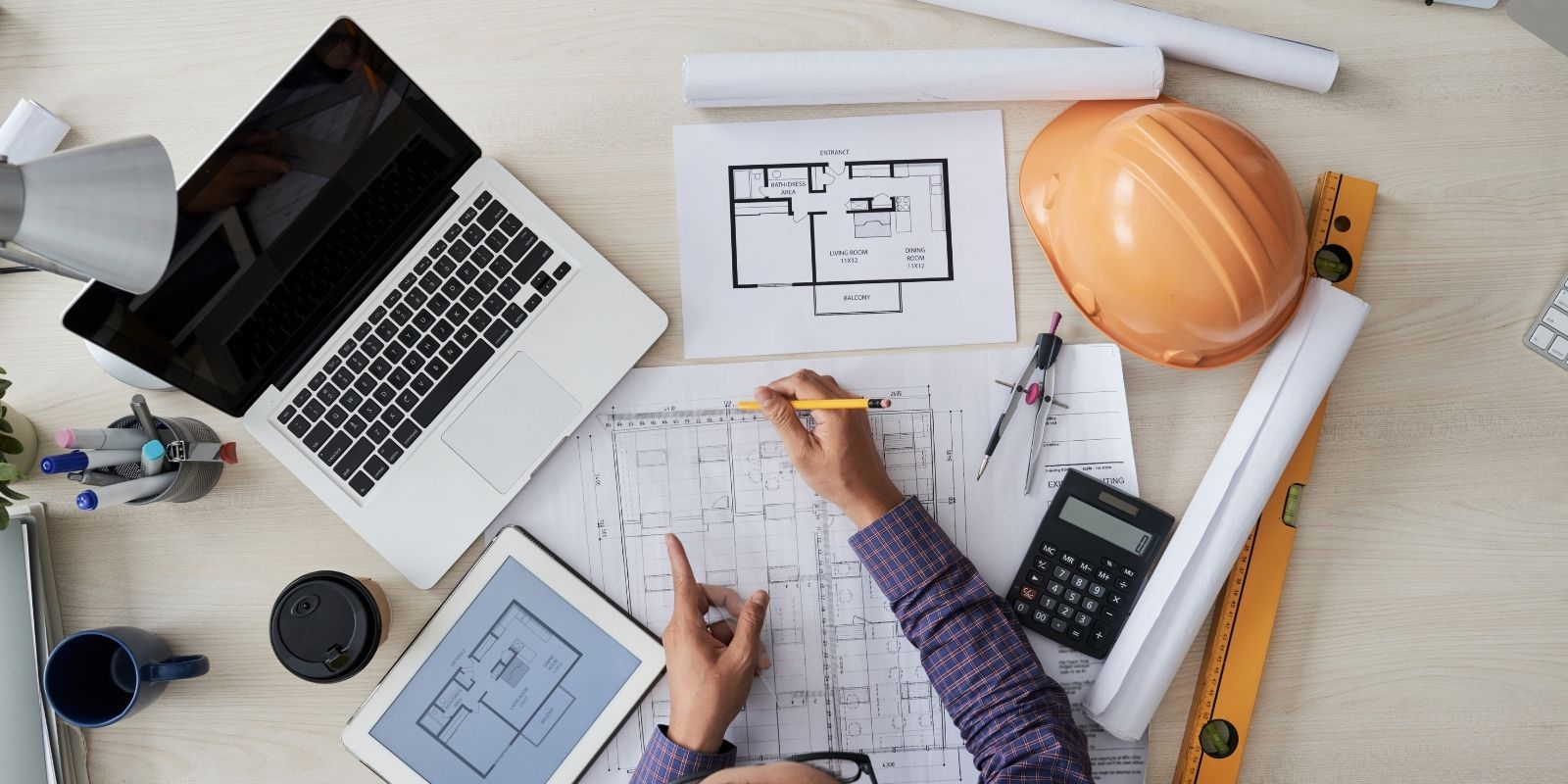 view of a civil engineer's desk with sketches, plans, computer, iPad and hardhat