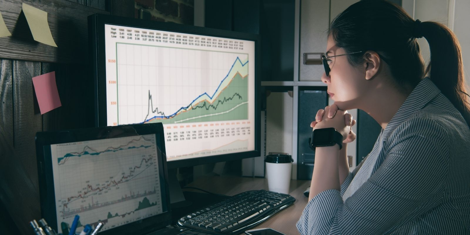 asian data scientist looks at graphs on her computer